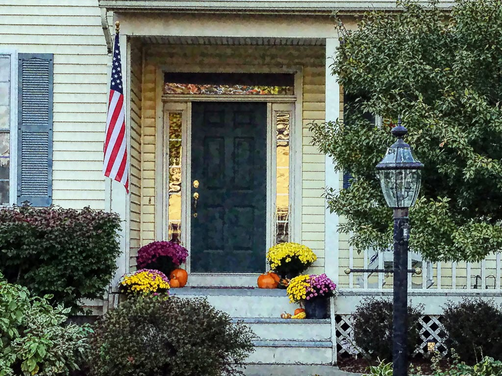 front door with US flag and garden on the side