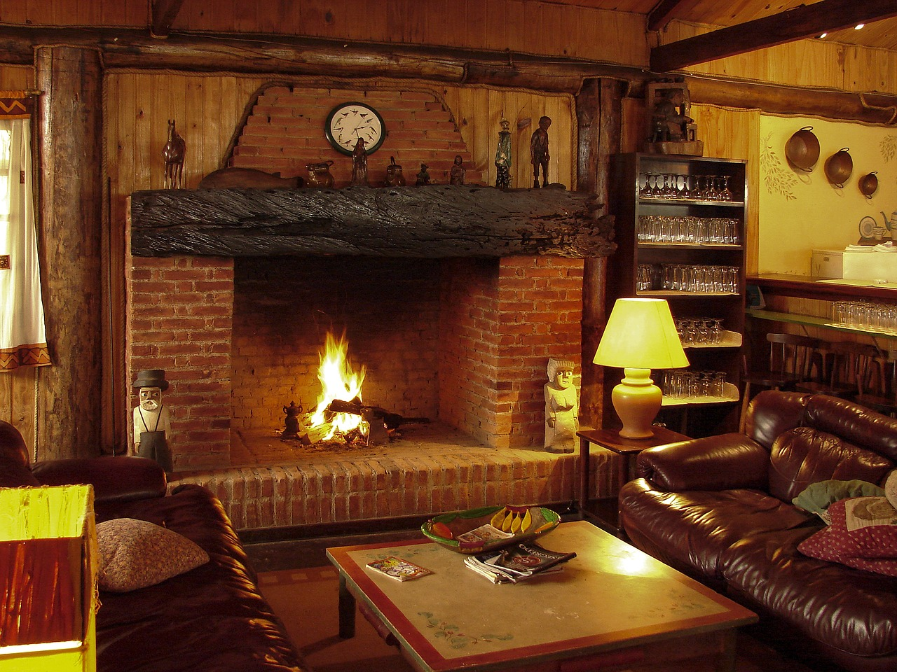 A rustic living room with a fireplace made of stones